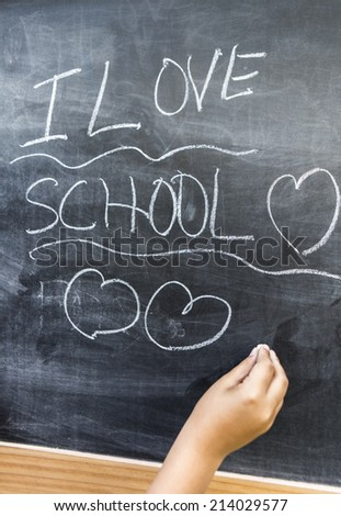 Boy writing I love school on a blackboard. - stock photo