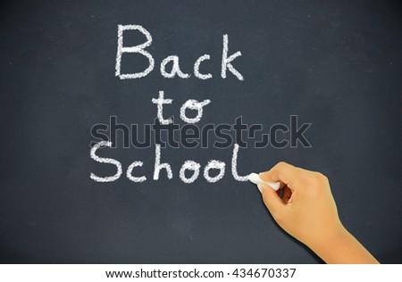 boy writing on a blackboard with chalk phrase Back to school - stock photo