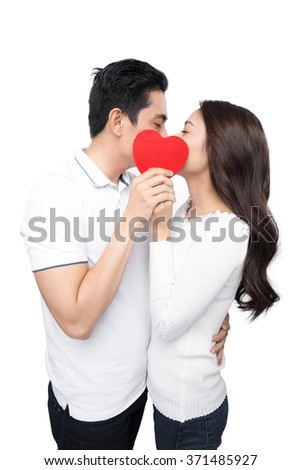 Boyfriend and girlfriend kissing looking each other in eyes. Couple of asian lovers at the beginning of love story having fun together. - stock photo