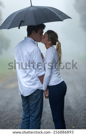boyfriend and girlfriend kissing under umbrella in the rain - stock photo