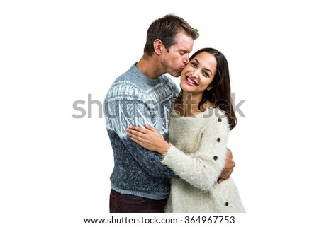 Boyfriend kissing girlfriend while standing against white background - stock photo