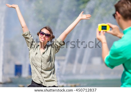 Boyfriend taking a picture of his girlfriend while sitting background the fountain. Young man making photo of woman on the street laughing and having fun in summer. - stock photo