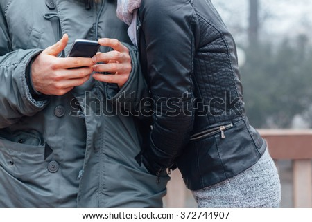 Boyfriend using mobile phone while his girlfriend warms hands in his jacket in close up - stock photo