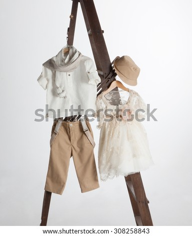 Boys and girl baptism clothes and accessories in old staircase - stock photo