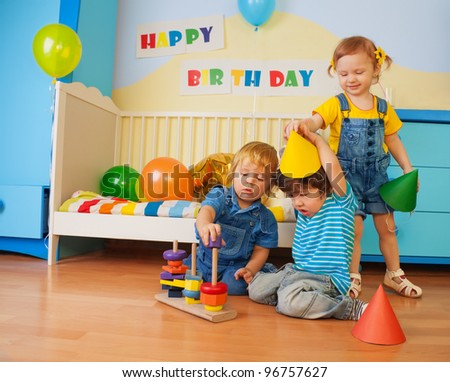 Boys and girl playing on birthday party constructing a pyramid and girl putting on celebration caps - stock photo