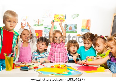 Boys and girls busy on creative class lesson painting and gluing - stock photo