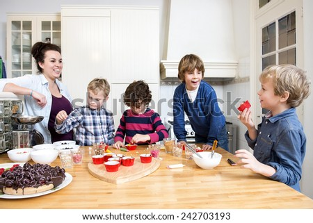 Boys and girls decorating cupcakes at a kitchen counter during a baking workshop for kids at a birthday party - stock photo
