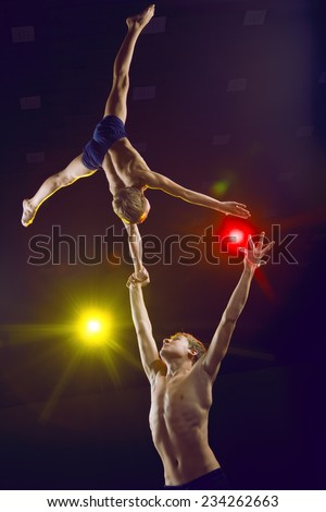 Boys athlete acrobats perform acrobatic figures in the arena - stock photo