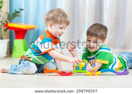 boys children playing rail road toy in nursery - stock photo