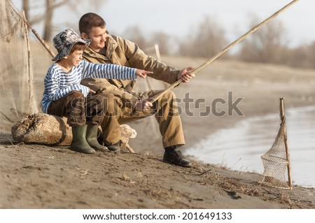 Boys fishing on the river bank at sunset - stock photo
