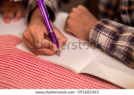 Boys' hand writing in notebook. Afro boy writes on paper. Young gentleman makes a reminder. Child writes a poem. - stock photo