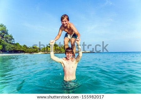boys have fun playing piggyback in the ocean - stock photo