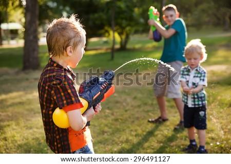 boys having fun playing with water guns - stock photo