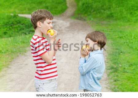 boys in the Park eating apples - stock photo