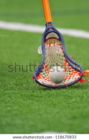 Boys lacrosse stick scoops the ball up off the field for control of the ball and game. - stock photo