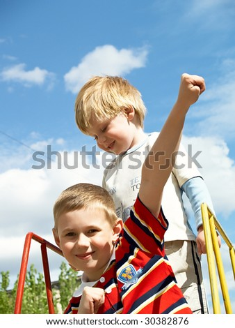 Boys play on a children's playground in the spring - stock photo
