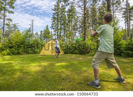 Boys playing a frisbee in the park - stock photo