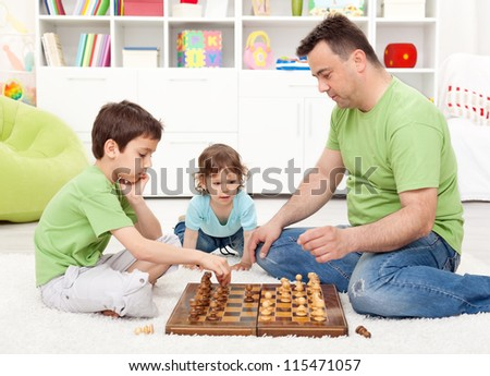 Boys playing chess with their father in the kids room - focus on smaller child - stock photo