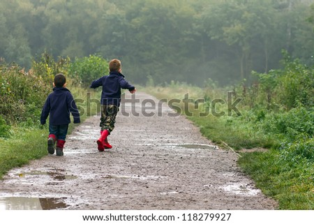 Boys playing in a muddy puddle - stock photo