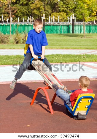 Boys playing on a seesaw on a playground in a sunny day - stock photo