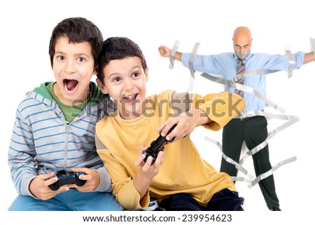 Boys playing video games and dad glued to the wall with duct tape in the background - stock photo