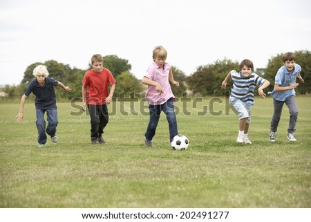 Boys playing with football in park - stock photo