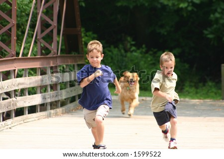 Boys Running with Dog - stock photo