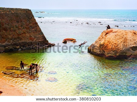 Boys swimming and jumping to the ocean from the rock. Sri Lanka - stock photo