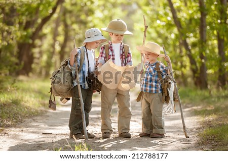 Boys travelers with backpacks studying the route map in a sunny summer day - stock photo