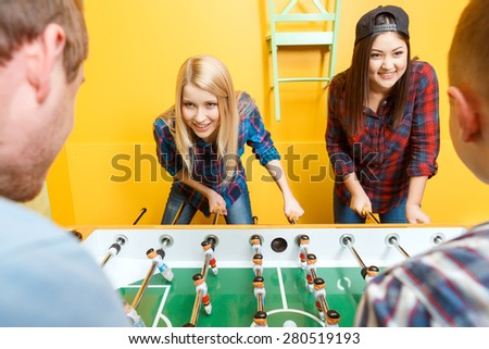 Boys vs girls. Young happy friends absorbedly playing table hockey two girls against two boys in a yellow room while a blond girl looking foxy selective focus - stock photo