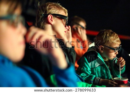 boys watching a movie in 3D glasses at the cinema - stock photo