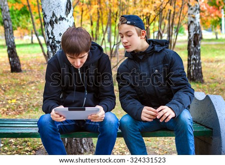 Boys with Tablet Computer in the Autumn Park - stock photo