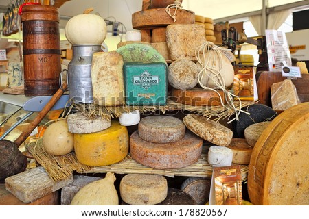 BRA, ITALY - SEPTEMBER 22, 2013: Different mature hard cheese types on the stand. Hard cheese (granular cheese) produced by stirring and draining mixture of curd and whey and has rich tangy taste. - stock photo