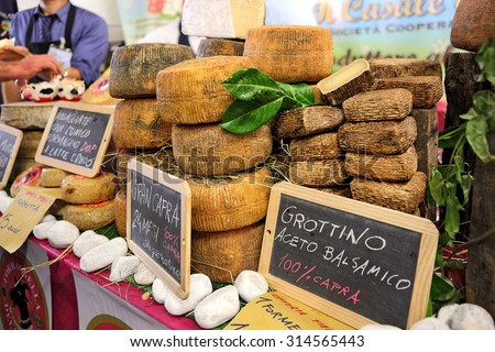 BRA, ITALY - SEPTEMBER 22, 2013: Gran Capra and Grottino - famous italian hard mature cheese with granular texture, often used for grating, made from goat. - stock photo