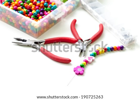 Bracelet made of wooden beads for girls unfinished in process of completing - stock photo