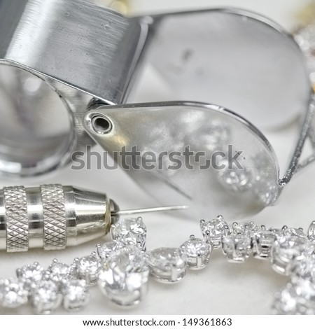 Bracelet with diamond and repairing jewelry tools (loupe,pliers) - stock photo