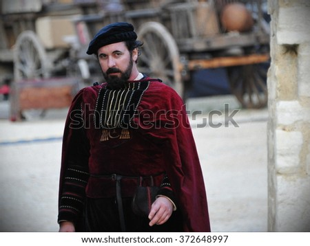 BRADFORD ON AVON, UK - JULY 1, 2014: An actor walks through a set during filming of Wolf Hall. The popular BBC series Wolf Hall is a period drama set in 16th century England. - stock photo