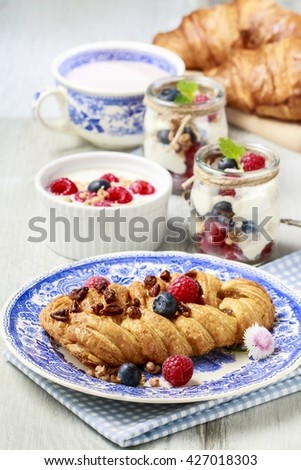 Braided danish bun made of puff pastry decorated with fresh fruits. Tasty breakfast. - stock photo