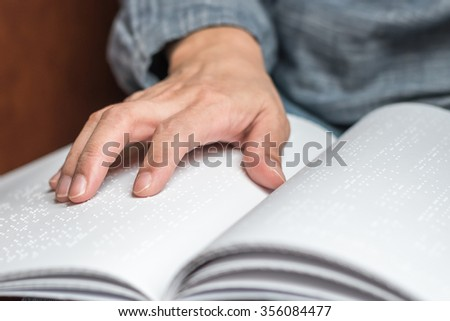 Braille book with visual impaired/ low vision person's hand/ finger touching paper texture reading the sign: The blind accessibility in equal educational literacy concept: Human rights to learn - stock photo