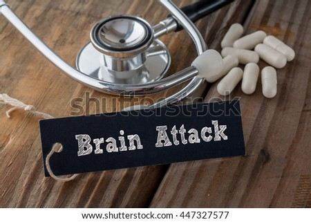 Brain Attack written on label tag with pills and Stethoscope on wood background - stock photo