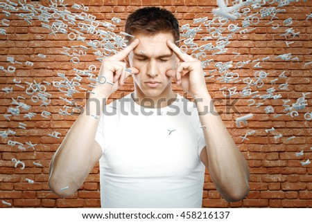 Brainstorm concept with thoughtful young guy surrounded with abstract letters on red brick wall background - stock photo
