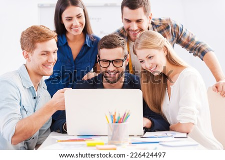 Brainstorm. Group of cheerful business people in smart casual wear looking at the laptop together and smiling  - stock photo