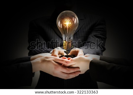 Brainstorming and teamwork concept with diverse business people holding light bulb in hands - stock photo