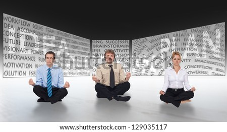 Brainstorming concept with meditating business people in front of large screens - stock photo