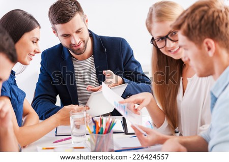 Brainstorming. Group of cheerful business people in smart casual wear working together while sitting at the table - stock photo