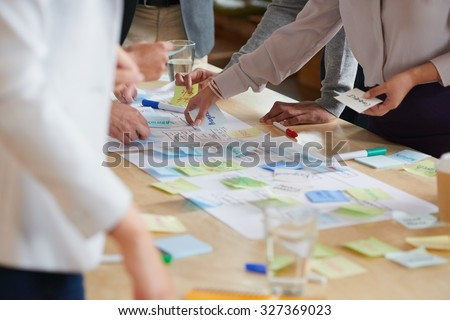 Brainstorming session with post it notes on desk - stock photo