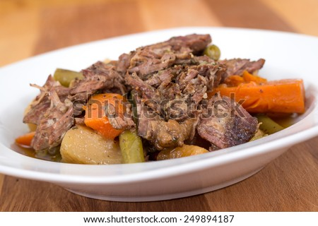 braised beef pot roast stew with vegetables on table - stock photo