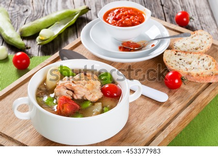 Braised chicken things with new potatoes, tomatoes and butter lima bean in graten dish and in soup bowl on table mat, tomato and bell pepper sauce in gravy boat, view from above - stock photo