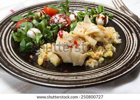 Braised cod with rice, cherry tomatoes and mozzarella salad - stock photo