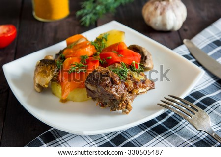 Braised lamb ribs with vegetables on white plate - stock photo